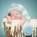 photo-04-newborn-smiling-in-the-basket-blue-background
